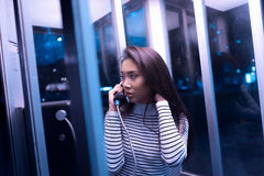 Woman in White and Black Stripe Long Sleeve Shirt Using Telephone Inside Telephone Booth during Night Time Stock Photography