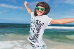 Woman in White and Black T-shirt Lifting Hands Smiling on Seashore Royalty Free Stock Images