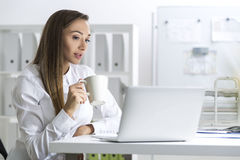 Woman in a white blouse with coffee and laptop Royalty Free Stock Photography