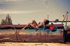 Woman in White and Blue Striped Two Piece Lying on Rustic Brown Metal Tank Royalty Free Stock Images