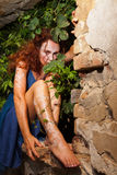 Wild beautiful woman. Woman with white body henna tattoos hiding in bush behind brick wall Stock Photos