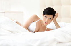 Woman in white bra is lying in the bedstead Royalty Free Stock Image