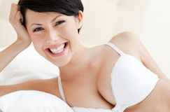Woman in white bra is lying in the double bed Stock Photo