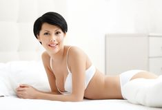 Woman in white bra is lying in the queensize bed Stock Photo