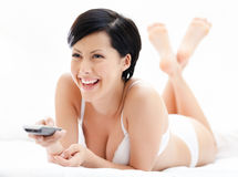 Woman in white bra is lying in the spacious bed Stock Photo