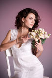 Woman in white bridal dress with flowers Stock Image