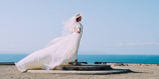 Woman in White Bridal Gown Standing in Brown Round Concrete Surface Under Blue Sky during Day Time Stock Image