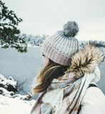 Woman in White and Brown Parka Jacket Wearing Grey Knitted Bobble Hat Near Blue Sea Under White Sky Royalty Free Stock Photos