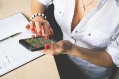 Woman in White Button Up Top and Holding Black Android Smartphone Stock Photography