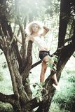 Woman in White Camisole and Black Denim Cut Off Shorts Standing on the Tree Trunk Royalty Free Stock Photography