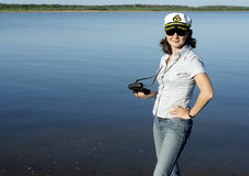 A woman in a white cap with binoculars stands on the banks of the river Royalty Free Stock Photos