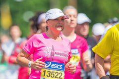 Woman with white cap and pink shirt in a group of runners in ASI Royalty Free Stock Image