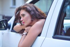 Woman in  white car looking bored Royalty Free Stock Images