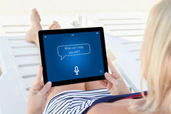Woman on white chaise lounge holding tablet app personal assista Royalty Free Stock Photos