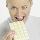 Woman with white chocolate. Portrait of young woman with white chocolate Stock Photography