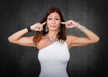 Woman in white closing ears Stock Photos