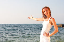 Woman in white cloth inviting to sea. Smiling wet woman in white cloth inviting to sea Royalty Free Stock Image