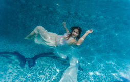 Woman in white cloth swimming underwater Royalty Free Stock Images