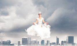 Young woman keeping mind conscious. Woman in white clothing keeping eyes closed and looking concentrated while meditating on cloud above wooden floor with Royalty Free Stock Photography