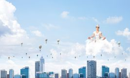 Young woman keeping mind conscious. Woman in white clothing keeping eyes closed and looking concentrated while meditating on cloud in the air with cityscape Stock Images