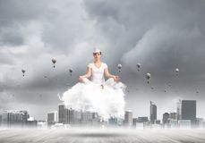 Young woman keeping mind conscious. Woman in white clothing keeping eyes closed and looking concentrated while meditating on cloud with cityscape view and Stock Photos