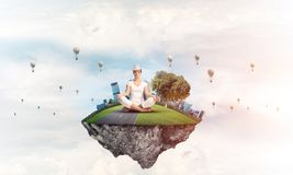 Young woman keeping mind conscious. Woman in white clothing keeping eyes closed and looking concentrated while meditating on island in the air with cloudy Royalty Free Stock Photography
