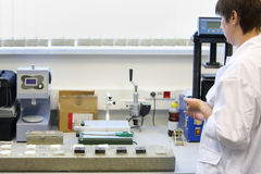 Woman in white clothing works in laboratory stock photography