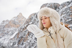 Woman in white coat and fur hat blowing snow from hand outdoors Royalty Free Stock Photography