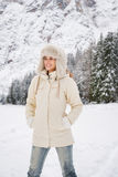 Woman in white coat and fur hat standing in winter outdoors Royalty Free Stock Photography