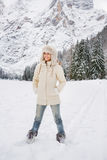 Woman in white coat and fur hat standing in winter outdoors. Magical mix of winter season and mountain landscape create the perfect mood. Full length portrait of Royalty Free Stock Photos