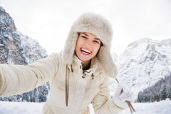Woman in white coat and fur hat taking selfie in winter outdoors Royalty Free Stock Photos
