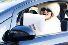 Woman in white coat with ipad laughing Royalty Free Stock Photography