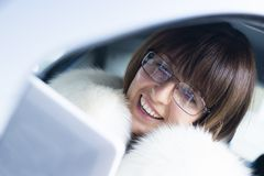 Woman in white coat with ipad laughing Stock Photo