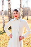 Woman in white coat outdoors Stock Photo