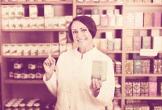Woman in white coat promoting food additive goods in carton in d Stock Images