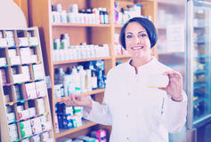 Woman in white coat promoting food additive goods in carton in d Stock Photo