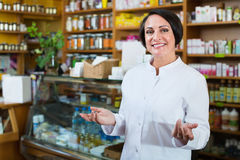Woman in white coat promoting health supplements in drugstore Royalty Free Stock Photography