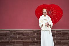 Woman in white coat with red umbrella Royalty Free Stock Image