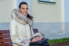 Woman in white coat sitting on bench Royalty Free Stock Photo