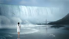 Woman in white coat  standing close to waterfall Royalty Free Stock Image