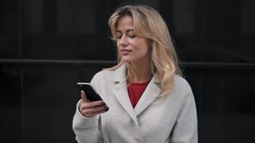 Woman in white coat standing and web surfing on her phone. Attractive blonde woman wearing white coat standing in autumn street and web surfing on her smartphone stock video