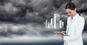 Woman in white coat with tablet and white building graphic against stormy sky Stock Photo