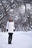 Woman in white winter park. Woman in white coat in white winter park Royalty Free Stock Images
