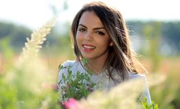 Woman in White Crew Neck Shirt Smiling and Surround With Flowers and Plants during Daytime Stock Image