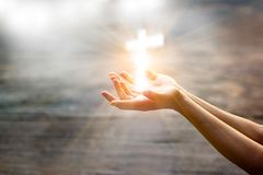 Woman with white cross in hands praying on sunlight. Woman with white cross in hands praying for blessing from god on sunlight background, hope concept royalty free stock photos