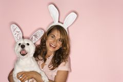 Woman and white dog wearing rabbit ears. Royalty Free Stock Image