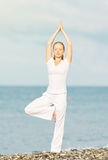 Woman in white doing yoga on  beach Royalty Free Stock Photo