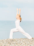 Woman in white doing yoga on  beach Royalty Free Stock Image