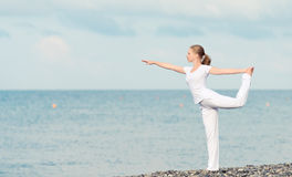 Woman in white doing yoga on  beach Stock Images