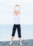 Woman in white doing yoga and sport exercises on  beach Royalty Free Stock Photography